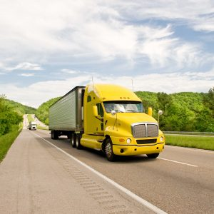 Yellow Semi Truck Travels On Interstate In Springtime
